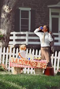 Man drinking lemonade from boy's lemonade stand